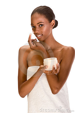 Afro-American girl wrapped in towel cream on face