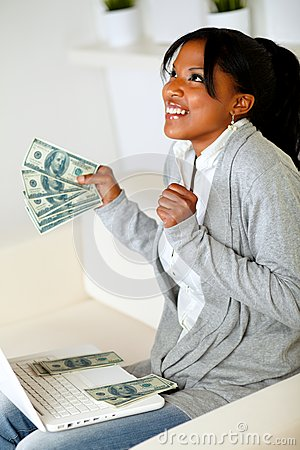 Afro-american woman looking up with dollars