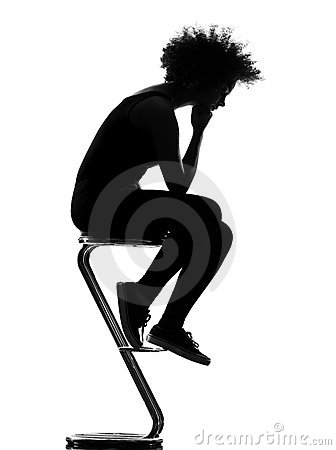 afro american woman sitting on footstool thinki