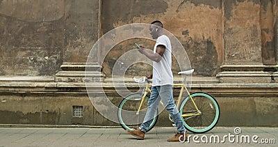 Afro American Young Man in Earphones mit seinem modernen Mobiltelefon und dem Modern Thin Tire Bike auf dem Laufsteg stock footage