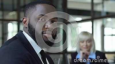 Afro-amerikaanse mannelijke werknemer die op camera kijkt, gelijke behandeling op het werk stock videobeelden