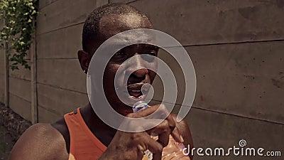 Afro-amerikanischer Profi-Läufer schwitzt durstigem Trinkwasser hält Flasche abkühlen nach hartem städtisches Training abkühl stock footage
