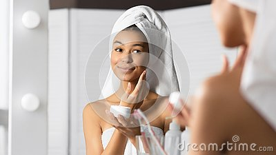 Afro Young Lady Applying Face Cream Standing In Bathroom, Panorama Stock Photo