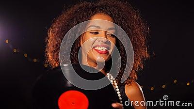 Afroamerykańska młoda kobieta trzyma winylowego rejestr i tana na czerni świateł tle w partyjnej sukni dziewczyna odizolowywający zbiory wideo