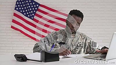 Afroer-amerikanisch Soldat in der Uniformfunktion ernsthaft im Büro stock footage