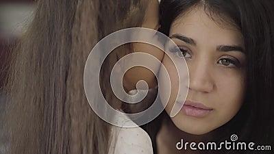 Afsluiten portret van een schattig meisje uit het Midden-Oosten met krullend haar dat fluistert in het oor van haar moeder Mooie  stock videobeelden