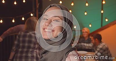 Afsluiten portret van jonge, mooie moslimvrouwen in hijab op een diverse partij in de cozy avond stock videobeelden