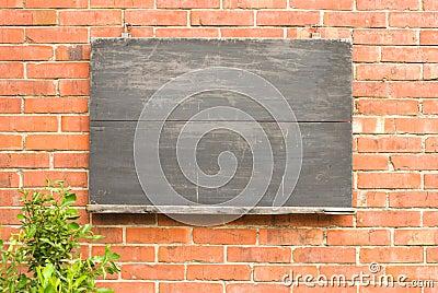Aged blackboard on red brick wall.