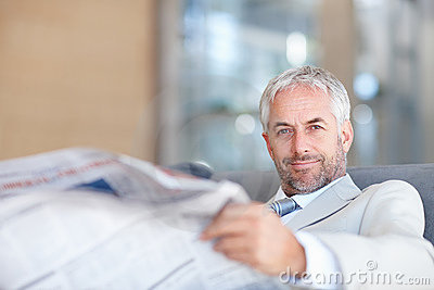 An aged business man reading newspaper