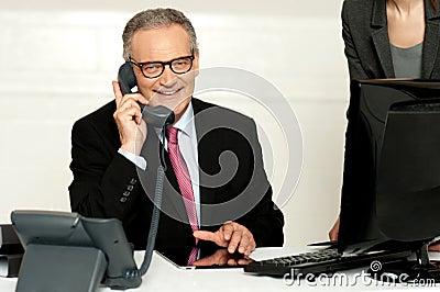 Aged businessman communicating on phone