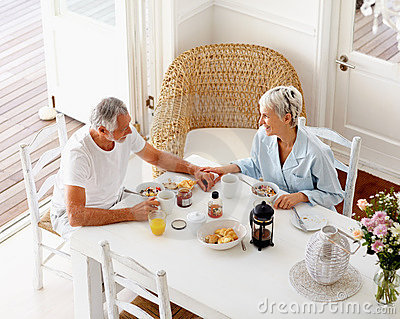 An aged couple enjoying their breakfast at home