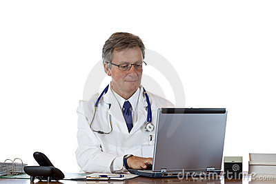 Aged doctor types medical history in laptop