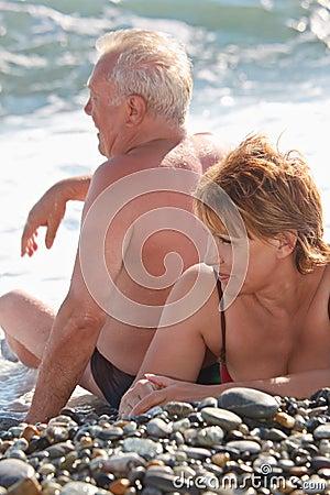 Aged pair sit on pebble beach