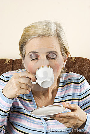Aged woman drink a hot coffee