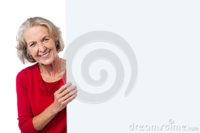 Aged woman holding blank ad board