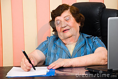 Aged woman writing on papers in office