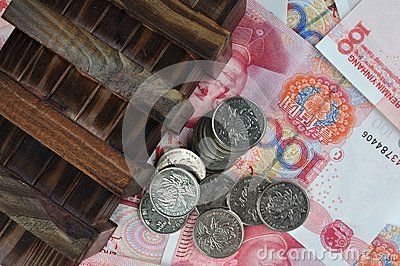 Aged wooden box and coins on money notes