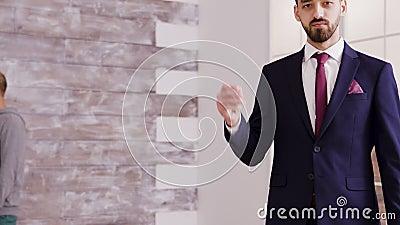 Agent immobilier en costume d'affaires souriant et affichant la clé d'appartement clips vidéos