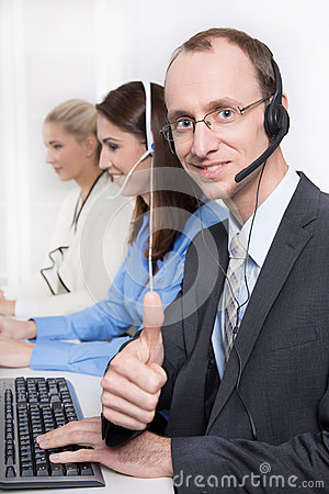 Agent smiling while working on his computer in a call-center.