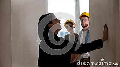 Agente inmobiliario mostrando un nuevo proyecto de departamento a una familia - conmovedor paredes y hablando metrajes