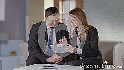 Agente inmobiliario que muestra las fotos en la tableta al cliente del hombre de negocios almacen de metraje de vídeo