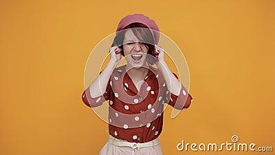 Agréable dame hurlant des oreilles avec des doigts, un geste drôle banque de vidéos