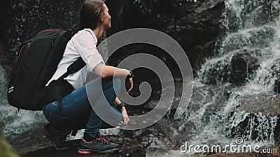 Agregação de caminhante feminina perto de uma cascata de salga selvagem vídeos de arquivo