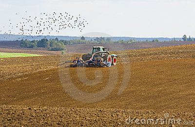 Agricultural tractor cultivating on farmland