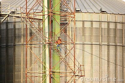 Agriculture Worker Climbing Stairway On Grain Bin Editorial Photography