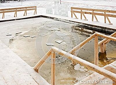 Agujero en el hielo en las maderas del invierno para el baño de la epifanía