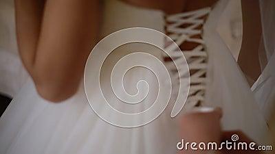 Aide de demoiselle d'honneur pour lacer la robe de mariage banque de vidéos