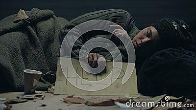 Aidez-moi à écrire sur une affiche tenant un pauvre mendiant sans abri, un passant fait don d'argent banque de vidéos