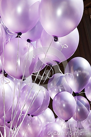The air is filled with festive purple balloons