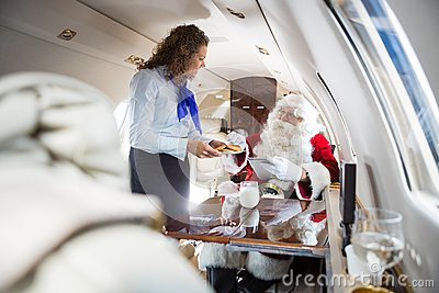 Air hostess Serving Cookies To Santa In Private Jet