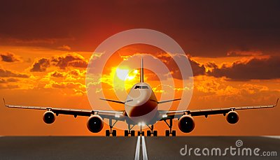 Air plane on runway at sunset