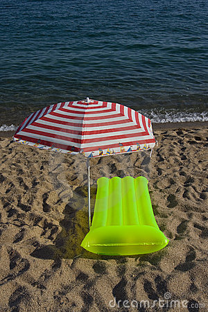 Airbed and sun umbrella on a beach