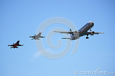 Airbus A320 aircraft accompanied by two fighters Editorial Photo