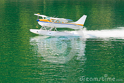Aircraft seaplane taking off on calm water of lake