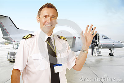 Airline pilot at the airport waving