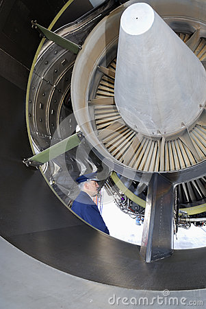 Airline pilot examining jet engine