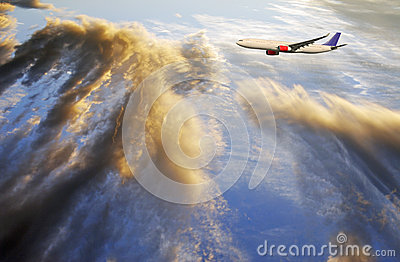 Airplane flying above sunset clouds