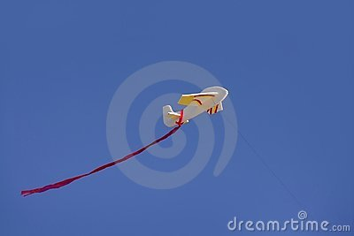 Airplane kite flying on blue sunny sky