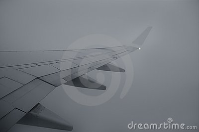 Airplane right wing flying over cloudy gray day