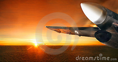 Airplane in sunrise sky. Panorama.
