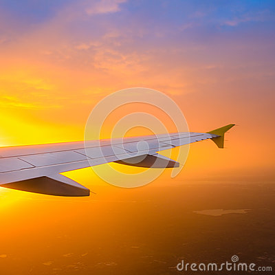Airplane wing against a sunrise sky