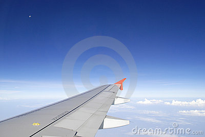 Airplane wing in the blue sky