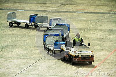 Airport baggage carrier train on tarmac Editorial Photo