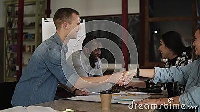 Aislamiento de un reparto Hombres de negocios que sacuden las manos, acabando para arriba de encontrarse en oficina o lugar de tr almacen de metraje de vídeo