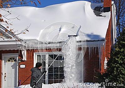 Ajuntando a neve fora do telhado