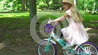 Aktywny piękny blond dziewczyny przejażdżki post jej bicykl w drzewnej alei Gimbal podąża zbiory